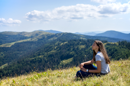 87995033 - the girl is sitting with closed eyes on the mountainside