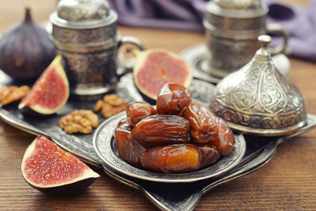 31211502 - cup of coffee with dry dates on metal oriental tray